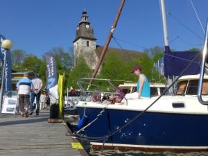 Vy av folklivet på bryggan med Mattias Brundell, Jarmo Linnermo (delvis skymda) och Virpi Salomaa på båtarna. I bakgrunden syns Nådendals magnifika klosterkyrka.